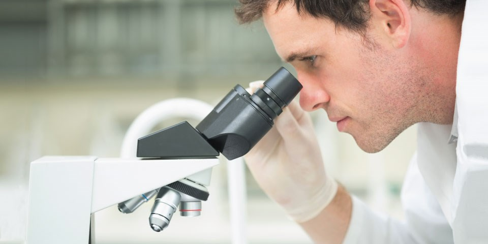 Man looking through microscope